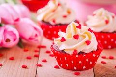Σπιτικός βαλεντίνος cupcakes με τις κόκκινες καρδιές ζάχαρης και τις ρόδινες τουλίπες Στοκ Εικόνες