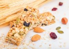 Σπιτικός οργανικός φραγμός δημητριακών granola με τα καρύδια και ξηρός - φρούτα στο άσπρο υπόβαθρο με τις βρώμες και τον ακατέργα στοκ εικόνα με δικαίωμα ελεύθερης χρήσης