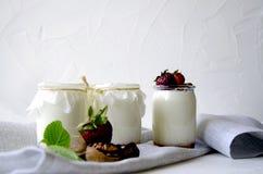 Σπιτικό γιαούρτι με τις φρέσκες φράουλες Τα συστατικά για ένα υγιές πρόγευμα είναι μισά των φραουλών, των ξύλων καρυδιάς και του  στοκ εικόνες