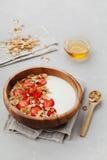 Σπιτικό γιαούρτι στο ξύλινο κύπελλο με τη φράουλα και το granola ή muesli στον ελαφρύ πίνακα, υγιές πρόγευμα στοκ εικόνες