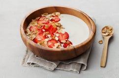 Σπιτικό γιαούρτι στο ξύλινο κύπελλο με τη φράουλα και το granola ή muesli στον ελαφρύ πίνακα, υγιές πρόγευμα στοκ εικόνα με δικαίωμα ελεύθερης χρήσης