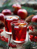 Σπιτικό θερμαμένο κρασί ή sangria με τις φέτες πορτοκαλιών και μήλων, τα βακκίνια, κανέλα Χριστουγέννων αντιγράφων διακοσμήσεων κ Στοκ Φωτογραφία
