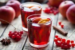Σπιτικό θερμαμένο κρασί ή sangria με τις φέτες πορτοκαλιών και μήλων, τα βακκίνια, κανέλα, γλυκάνισο στον ξύλινο πίνακα Στοκ εικόνες με δικαίωμα ελεύθερης χρήσης
