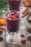 Σπιτικό θερμαμένο κρασί με τις πορτοκαλιά φέτες, τα τα βακκίνια, την κανέλα και το γλυκάνισο Στοκ εικόνα με δικαίωμα ελεύθερης χρήσης