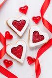 Σπιτικό διαμορφωμένο καρδιά δώρο μπισκότων με τη μαρμελάδα και κόκκινες κορδέλλες για Στοκ Φωτογραφία