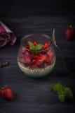 Σπιτικό ιταλικό cotta panna επιδορπίων με τις φρέσκες φράουλες και μέντα σε ένα σκοτεινό ξύλινο υπόβαθρο Στοκ Φωτογραφία