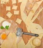 Σπιτικό ιταλικό ravioli με το φρέσκο τυρί, το αλεύρι, το αυγό, την ακατέργαστη ζύμη και τα αρωματικά χορτάρια, που τοποθετούνται  Στοκ Εικόνες