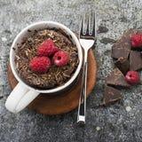 Σπιτικό κέικ κουπών σοκολάτας με τα τσιπ σοκολάτας, juicy φρέσκα σμέουρα σε μια μοντέρνη ριγωτή γκρίζα κούπα με τα κομμάτια Στοκ φωτογραφία με δικαίωμα ελεύθερης χρήσης