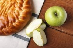 Σπιτικό κέικ μήλων και πράσινο μήλο πέρα από το φυσικό ξύλινο υπόβαθρο Στοκ εικόνα με δικαίωμα ελεύθερης χρήσης