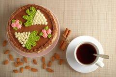 Σπιτικό κέικ του Κίεβου, φλυτζάνι του τσαγιού και διεσπαρμένα αμύγδαλα στην υφαντική πετσέτα Στοκ Εικόνα