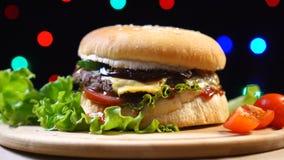Σπιτικό και φρέσκο νόστιμο burger με το τυρί, ντομάτα, μαρούλι στο ζωηρόχρωμο θολωμένο υπόβαθρο φω'των φιλμ μικρού μήκους