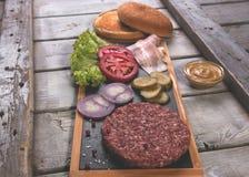Σπιτικό κουλούρι συστατικών χάμπουργκερ φρέσκο, αλατισμένο αγγούρι, patties βόειου κρέατος, μπέϊκον Στοκ φωτογραφία με δικαίωμα ελεύθερης χρήσης