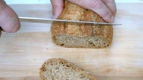 Σπιτικό μαγείρεμα Τα αρσενικά χέρια είναι τέμνον ολόκληρο φρέσκο ψωμί σιταριού, με το μαχαίρι κουζινών στον ξύλινο πίνακα Εγχώριο φιλμ μικρού μήκους