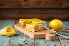 Σπιτικό νόστιμο βαλμένο σε στρώσεις κέικ λεμονιών και ολόκληρα και συμπιεσμένα λεμόνια Στοκ εικόνα με δικαίωμα ελεύθερης χρήσης