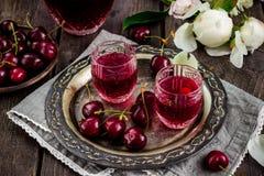 Σπιτικό ποτό κερασιών εκλεκτής ποιότητας γυαλιά στο δίσκο και τα κεράσια μετάλλων στοκ εικόνες