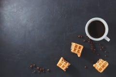 Σπιτικό πρόγευμα, μαύρος πίνακας πετρών Τα βιενέζικα σπασμένα βάφλες κομμάτια, ένα φλιτζάνι του καφέ, διασκόρπισαν τα φασόλια καφ στοκ φωτογραφία με δικαίωμα ελεύθερης χρήσης
