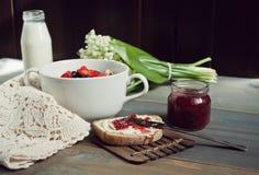Σπιτικό σιταρένιο ψωμί που τεμαχίζεται και που ολοκληρώνεται με το βούτυρο και τη μαρμελάδα, το granola με τα μούρα και το ποτήρι Στοκ Φωτογραφίες