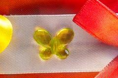 Σπιτικό στοιχείο ραπτικής του τυλίγματος δώρων, της κίτρινης πεταλούδας φιαγμένων από γυαλί και των τόξων κορδελλών φιαγμένων από στοκ εικόνα
