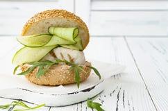 Σπιτικό τριζάτο burger ψαριών άνοιξη με τα πικάντικα τσίλι mayo στο λευκό αγροτικό ξύλινο πίνακα πέρα από το ελαφρύ υπόβαθρο διάσ Στοκ Φωτογραφία