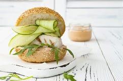 Σπιτικό τριζάτο burger ψαριών άνοιξη με τα πικάντικα τσίλι mayo στο λευκό αγροτικό ξύλινο πίνακα πέρα από το ελαφρύ υπόβαθρο διάσ Στοκ εικόνα με δικαίωμα ελεύθερης χρήσης