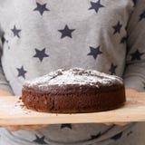 Σπιτικό φρέσκο κέικ γενεθλίων σοκολάτας με τη σκόνη άσπρης ζάχαρης στην κορυφή στα χέρια μιας γυναίκας Ένα συμπαθητικό κέικ για τ Στοκ εικόνα με δικαίωμα ελεύθερης χρήσης