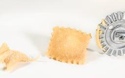 Σπιτικό φρέσκο ravioli με τον κόπτη ζύμης ροδών, στο άσπρο υπόβαθρο Στοκ Εικόνα