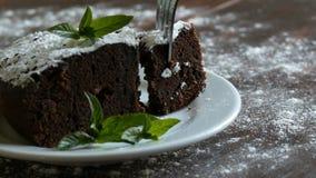 Σπιτικό ψημένο brownie σοκολάτας κέικ που καλύπτεται με την κονιοποιημένη ζάχαρη σε ένα άσπρο πιάτο που διακοσμείται με τα φύλλα  απόθεμα βίντεο