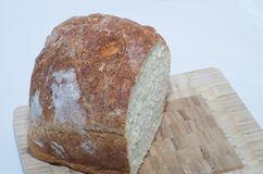 Σπιτικό ψωμί στον τέμνοντα πίνακα με το άσπρο υπόβαθρο Στοκ εικόνα με δικαίωμα ελεύθερης χρήσης