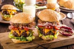 Σπιτικό burger βόειου κρέατος, καραμελοποιημένο κρεμμύδι, μπέϊκον και μπύρα στοκ εικόνα