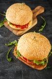 Σπιτικό burger με το arugula, την ντομάτα και το τυρί Στοκ Φωτογραφίες