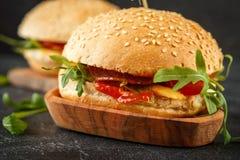Σπιτικό burger με το arugula, την ντομάτα και το τυρί Στοκ εικόνα με δικαίωμα ελεύθερης χρήσης