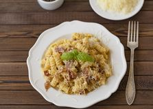 Σπιτικό carbonara ιταλικά ζυμαρικών με το μπέϊκον, αυγά, τυρί παρμεζάνας στο άσπρο πιάτο σε ένα σκοτεινό υπόβαθρο στοκ φωτογραφίες