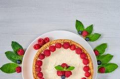 Σπιτικό cheesecake με τα φρέσκα μούρα στο άσπρο πιάτο που διακοσμείται με τα σμέουρα και τα βακκίνια, μέντα στον γκρίζο πίνακα Στοκ φωτογραφία με δικαίωμα ελεύθερης χρήσης
