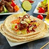 Σπιτικό Kofta kebabs στα οβελίδια με το pita, τον ασβέστη, τα λαχανικά, την μπύρα, το γλυκές τσίλι και τη σάλτσα γιαουρτιού στο ά Στοκ Εικόνα