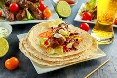 Σπιτικό Kofta kebabs στα οβελίδια με το pita, τον ασβέστη, τα λαχανικά, την μπύρα, το γλυκές τσίλι και τη σάλτσα γιαουρτιού στο ά Στοκ φωτογραφία με δικαίωμα ελεύθερης χρήσης