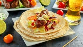 Σπιτικό Kofta kebabs στα οβελίδια με το pita, τον ασβέστη, τα λαχανικά, την μπύρα, το γλυκές τσίλι και τη σάλτσα γιαουρτιού στο ά Στοκ Εικόνες