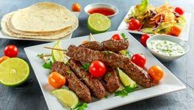 Σπιτικό Kofta kebabs στα οβελίδια με το pita, τον ασβέστη, τα λαχανικά, το γλυκές τσίλι και τη σάλτσα γιαουρτιού στο άσπρο πιάτο Στοκ Εικόνες