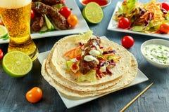Σπιτικό Kofta kebabs στα οβελίδια με το pita, τον ασβέστη, τα λαχανικά, το γλυκές τσίλι και τη σάλτσα γιαουρτιού στο άσπρο πιάτο Στοκ Φωτογραφίες