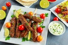 Σπιτικό Kofta kebabs στα οβελίδια με το pita, τον ασβέστη, τα λαχανικά, το γλυκές τσίλι και τη σάλτσα γιαουρτιού στο άσπρο πιάτο Στοκ εικόνα με δικαίωμα ελεύθερης χρήσης