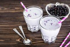 Σπιτικό milkshake με τα μούρα στο ξύλινο υπόβαθρο Στοκ Φωτογραφίες