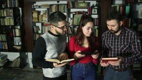 Σπουδαστές μαζί στη βιβλιοθήκη που ψάχνει για τις πληροφορίες και που κάνει τη φωτογραφία από τα βιβλία φιλμ μικρού μήκους