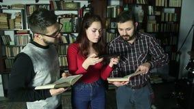 Σπουδαστές μαζί στη βιβλιοθήκη που ψάχνει για τις πληροφορίες και που κάνει τη φωτογραφία από τα βιβλία απόθεμα βίντεο