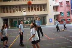 Σπουδαστές με ομοιόμορφο έχοντας την παίζοντας καλαθοσφαίριση διασκέδασης Στοκ Εικόνες