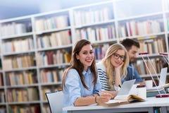 Σπουδαστές που εργάζονται στη βιβλιοθήκη στην πανεπιστημιούπολη Στοκ φωτογραφία με δικαίωμα ελεύθερης χρήσης