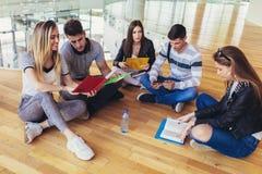 Σπουδαστές που κάθονται στο πάτωμα στην πανεπιστημιούπολη και που προετοιμάζονται μαζί για τους διαγωνισμούς στοκ εικόνα