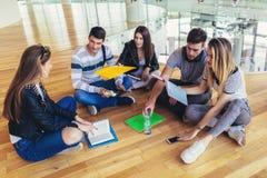 Σπουδαστές που κάθονται στο πάτωμα στην πανεπιστημιούπολη και που προετοιμάζονται μαζί για τους διαγωνισμούς στοκ εικόνες με δικαίωμα ελεύθερης χρήσης