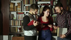 Σπουδαστές που μιλούν μαζί στη βιβλιοθήκη απόθεμα βίντεο