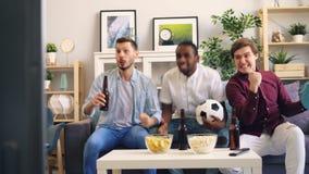 Σπουδαστές που πίνουν το ποδόσφαιρο προσοχής μπύρας στη TV που κάνει υψ απόθεμα βίντεο
