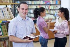 σπουδαστές τρία βιβλιο&thet στοκ εικόνες