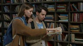Σπουδαστές Hipster που μελετούν στη βιβλιοθήκη στο πανεπιστήμιο απόθεμα βίντεο
